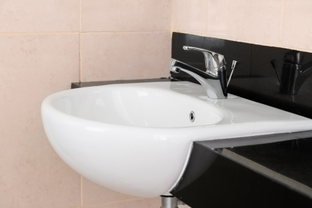 Modern ceramic hand wash basin with chrome water mixer tap in hotel washroom interior  photo