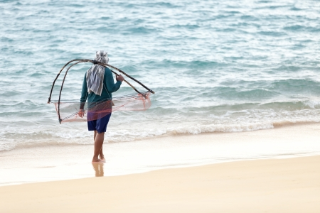 thailander: Man with net walk on the sea sand coast, Thailand Stock Photo