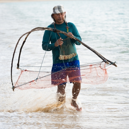 thailander: PHUKET, THAILAND - FEB 15: Native local man nets small crustaceous in the sea on Feb 28, 2013 in Phuket, Thailand. Fishing and nets are popular among Thailanders  Editorial