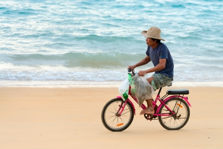 thailander: PHUKET, THAILAND - FEB 15: Old native local man bicycling along a sand beach on Feb 28, 2013 in Phuket, Thailand. Small law bicycles are common among Thailanders