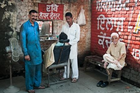 AMRITSAR, INDIA - AUG 28: Barber shaving a man in the street mobile barber
