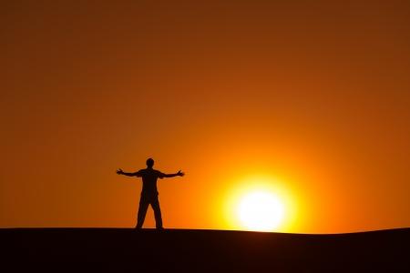 certainty: Man at orange sunset in desert with heroic achievement gesture