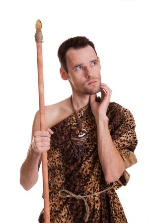 Edad de Piedra: Pensando en el hombre como un cazador salvaje en la piel de un animal con la lanza aislado en el fondo blanco Foto de archivo