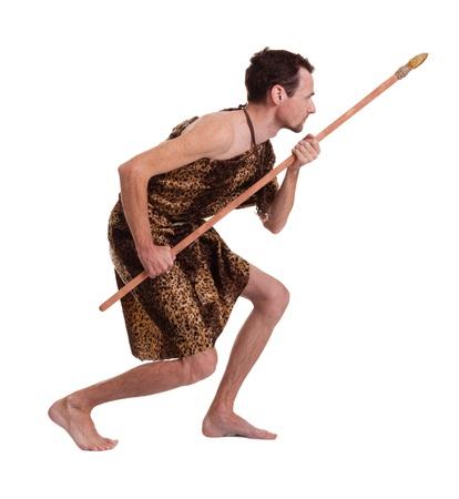 cazador: Tras hombre como cazador salvaje en la piel de un animal con la lanza aislado en el fondo blanco Foto de archivo