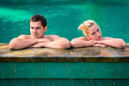 exasperated: Quarrel in vacation  angry and exasperated young couple in a swimming pool on a poolside in tropical resort Stock Photo