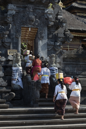 come in: BALI, INDONESIA - SEP 26: Women with offers come in the temple gate for sacred ceremony in Goa Lawah Bat Cave on Sep 26, 2012 in Bali, Indonesia Editorial