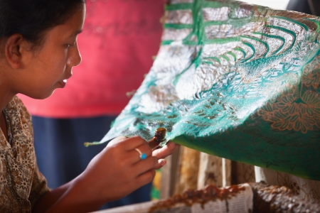 BALI, INDONESIA - Sep 21: Balinese woman applies wax on a piece of batik, on Sep 21, 2012 in Bali, Indonesia. Batik-making is an important part of Indonesian culture.  Editoriali