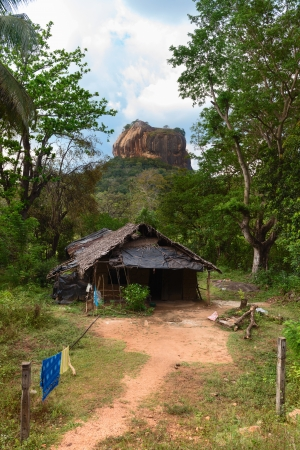 Shack in front of high rock under green forest. Sigiriya, Lions rock with ancient rock fortress castle. Sri Lanka  photo