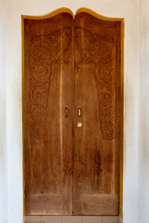 Old grunge wooden door with carving in arch photo