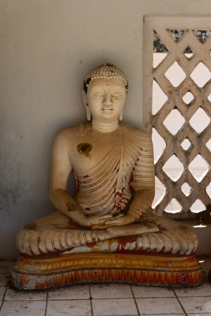 aukana buddha: Small grunge Buddha statue in a niche, Avukana, Sri Lanka Stock Photo