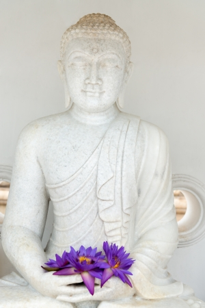 Buddha image statue with fresh flue star water lily or star lotus flowers in hands