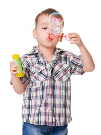 Portrait of funny little boy blowing soap bubbles isolated on ehite background