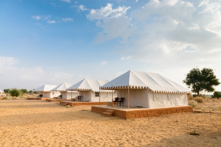 Tent camping site hotel for tourist  in the thar desert under blue sky photo
