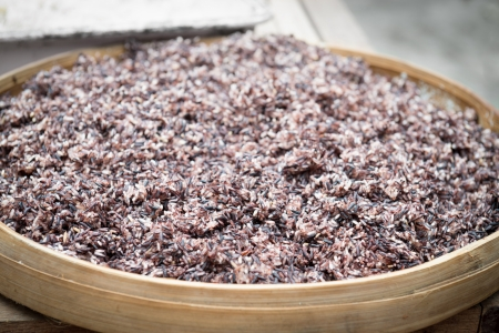 Cooked steam black rice in big wooden plate dish with shallow depth of field photo