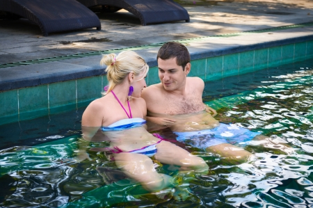 Happy smiling couple looking on each other while relaxing on the edge of a outdoor swimming pool  photo