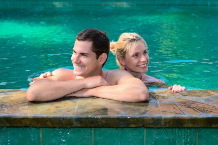 Happy smiling couple looking aside while relaxing on the edge of a outdoor swimming pool  photo