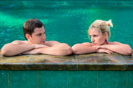 strife: Sad couple looking at each other on the edge of a outdoor swimming pool
