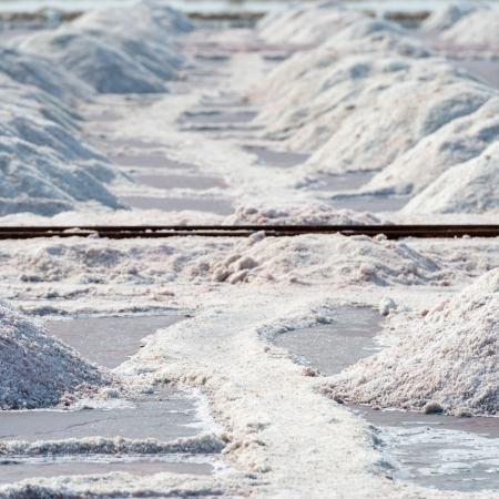 tonnes: Salt piles in salt farm on Sambhar Salt Lake, India. It is Indias largest saline lake and it produces 196 k tonnes of clean salt every year.