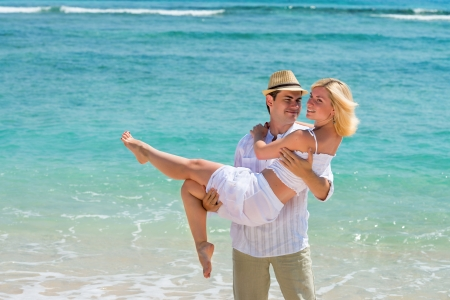 Happy young man carry woman. Couple enjoying at beach with blue sea on background.
