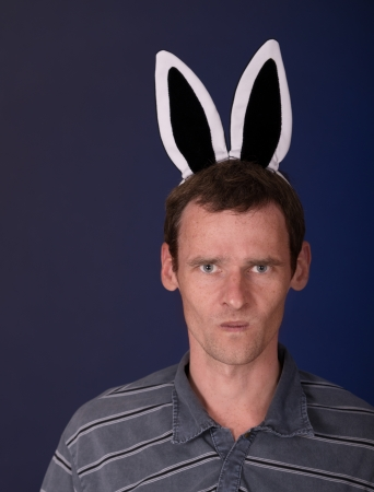 infuriate: Angry man of motley with rabbit ears on dark background Stock Photo