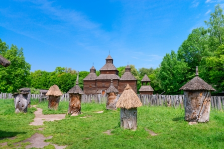 Ancient apiary in wooden bee hive with wooden buildings on background