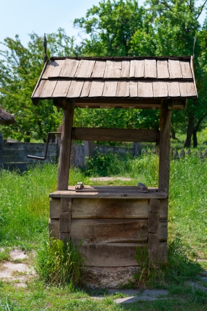 Old village well with a wood roof with green garden on background photo