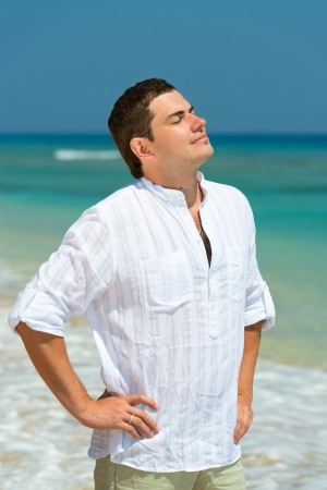 Handsome man enjoy vacation on a beach, with blue sea on background  photo