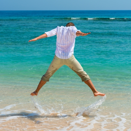 Man has fun in the blue sea by jumping up and spashing water photo