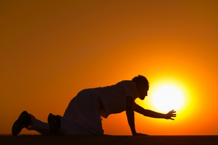 to creep: Tired and weaken man on all fours reached his hand to gold sunset sun disk to pray for help