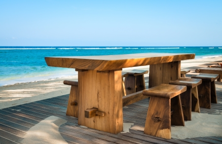 Wooden cafe table and chairs on a tropical beach with blue sea on background Stock Photo - 22644280