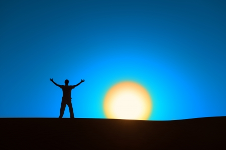 certainty: Man at blue background with big sun under horizon with heroic achievement gesture