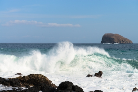 Waves breaking on a stony beach under blue sky and island on background photo