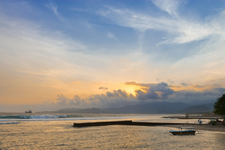 breakwaters: Sunset on a tropical sea shore with breakwaters and boats on Bali in Candidasa, Indonesia