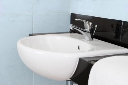 Modern ceramic hand wash basin with chrome water mixer tap in hotel washroom interior  Stock Photo - 22645647