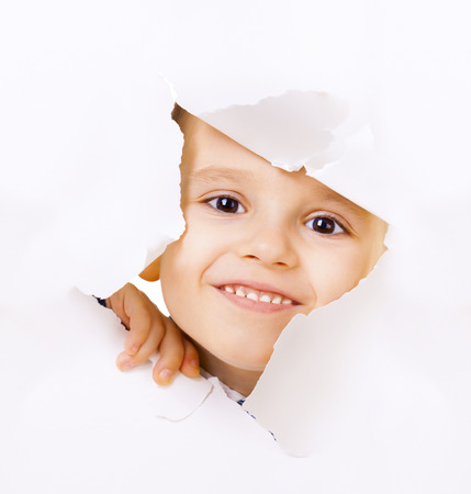 Smiling kid looking out of a hole of white paper photo