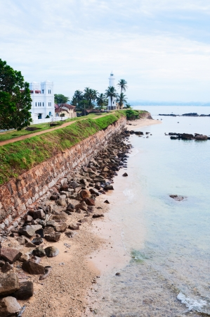 Sea shore with high wall and white lighthouse, Galle fortress, Sri Lanka photo