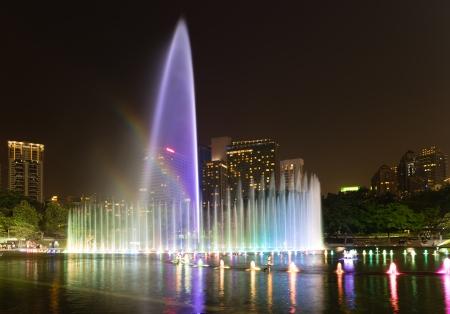 Illuminated fountain with rainbow at night in modern city skyline photo