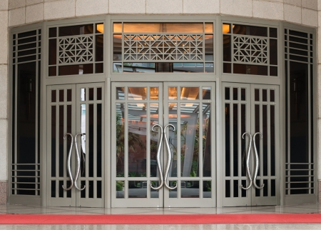 Elegant large two-leaf door in classical style with red carpet of the front photo