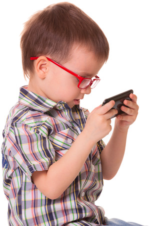 Clever kid is playing with black smart cell phone isolated on white  photo