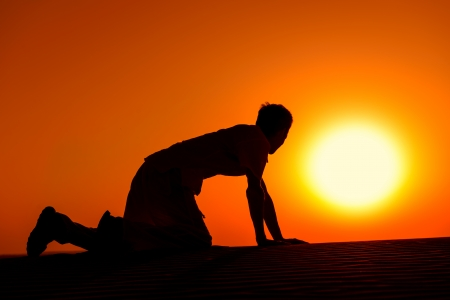 to creep: Tired and weaken man on all fours with gold sunset sun disk on background Stock Photo