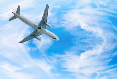 White jet airplane fly in blue bright wispy cloudy blue sky photo