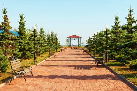 Wide path in nice light  park with benches and summerhouse under clean blue sky photo