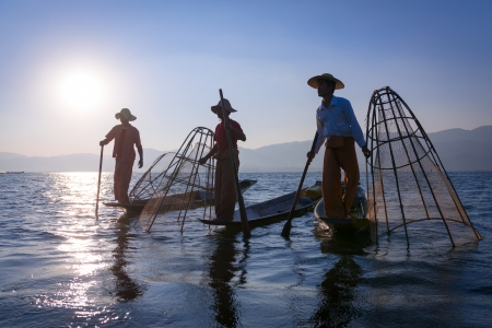 Silhouette of traditional fishermans in wooden boat using a coop-like trap with net to catch fish in Inle lake, Myanmar