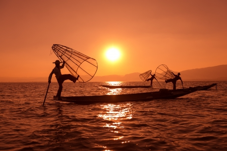 fishermans net: Silhouette of traditional fishermans in wooden boat using a coop-like trap with net to catch fish in Inle lake, Myanmar