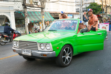 PHUKET, THAILAND - 07 FEB 2014: Phuket town residents on green car take part in procession of annual old Phuket town festival.