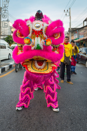 PHUKET, THAILAND - 07 FEB 2014: Dragon image in bright costume take part in procession parade of annual old Phuket town festival.