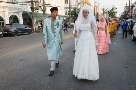 PHUKET, THAILAND - 07 FEB 2014: Phuket town residents in wedding dress take part in procession parade of annual old Phuket town festival.