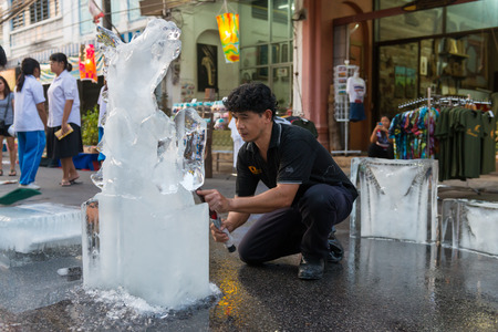 PHUKET, THAILAND - 07 FEB 2014: Unidentified men cut out icy horse for annual old Phuket town festival.