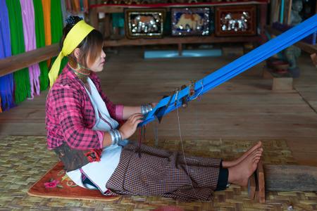 INLE LAKE, MYANMAR (BURMA) - 07 JAN 2014: Unidentified Padaung (Kayan Lahwi) tribe woman weave on traditional device. This tribe is called long neck€ because of metal rings around their necks.