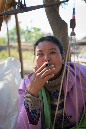 cheroot: INLE LAKE, MYANMAR (BURMA) - 07 JAN 2014: Local Burmese Intha market woman smoke cheroot cigar with scale details on front. Cheroots are Burmese facial feature.